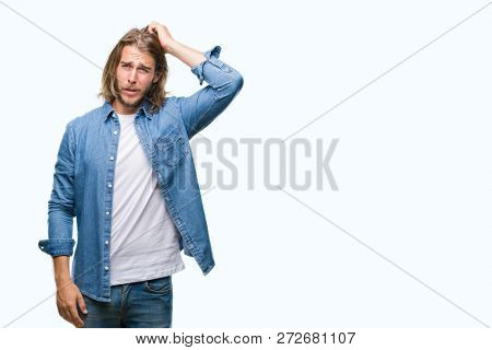 Young handsome man with long hair over isolated background confuse and wonder about question. Uncertain with doubt, thinking with hand on head. Pensive concept.