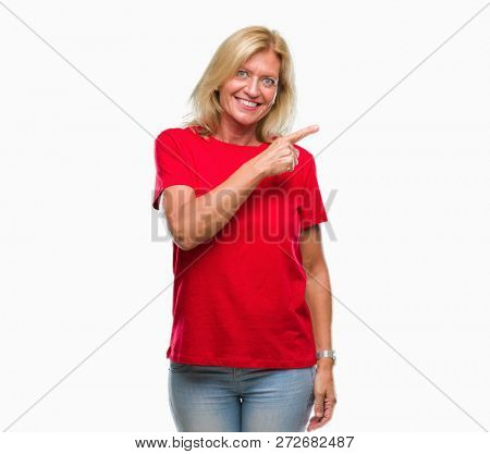 Middle age blonde woman over isolated background cheerful with a smile of face pointing with hand and finger up to the side with happy and natural expression on face looking at the camera.