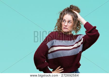 Beautiful brunette curly hair young girl wearing glasses over isolated background confuse and wonder about question. Uncertain with doubt, thinking with hand on head. Pensive concept.