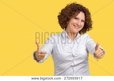 Beautiful middle ager senior businees woman over isolated background approving doing positive gesture with hand, thumbs up smiling and happy for success. Looking at the camera, winner gesture.