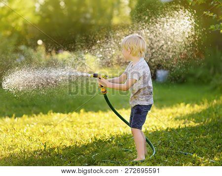 Funny Little Boy Playing With Garden Hose In Sunny Backyard. Preschooler Child Having Fun With Spray