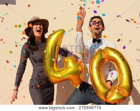 Cheerful Couple Celebrates A Forty Years Birthday With Big Golden Balloons And Colorful Little Piece