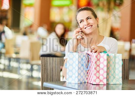 Happy woman shopping in the shopping mall is talking on the mobile phone