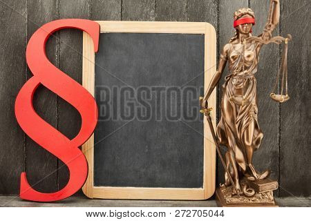 Justitia and paragraph as law and law concept beside an empty blackboard