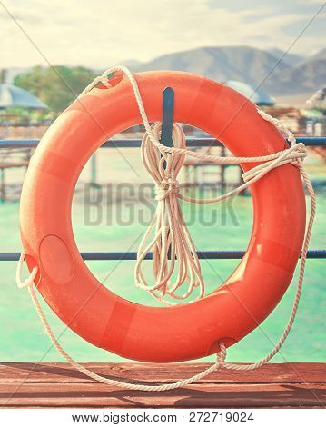 Orange Lifebuoy With Rope On A Wooden Pier Near Sea. Close Up Of Lifebuoy On Wooden Pier At The Beac
