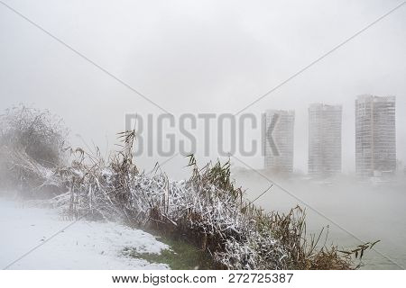 Poorly Visible High-rise Buildings On The Shore Of A Winter Lake. Snow Flakes Are Falling From The S