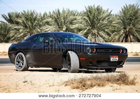 Dubai, Uae - November 15, 2018: Black Sportscar Dodge Challenger In The Sand Desert.