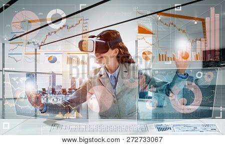 Business Woman In Suit Using Virtual Reality Goggles While Sitting Inside Bright Office Building. Co