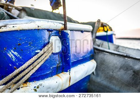 Fishing Boat Moored Or Docked At Pier In Sunset. Commercial Fishing Ship Is Tied To Pier With Thick