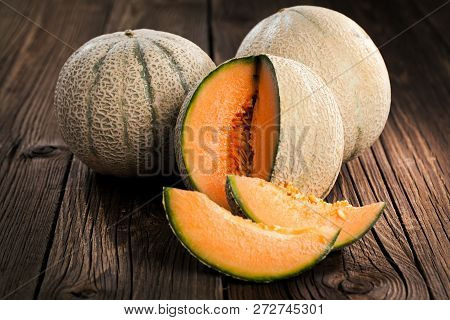Melon With Melon Slices And Leaves On A Old Wooden Table. Organic Food.