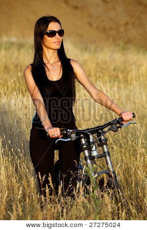 Portrait of a pretty young brown haired woman riding a bike with text space