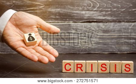Businessman Holds In His Hands A Cube With The Image Of The Dollar And The Word Crisis. Fall Busines