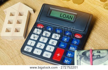 Money And Houses On The Table And A Calculator With The Word Loan. The Concept Of Buying Property In