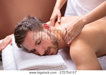 Close-up Of A Relaxed Young Man Receiving Shoulder Massage