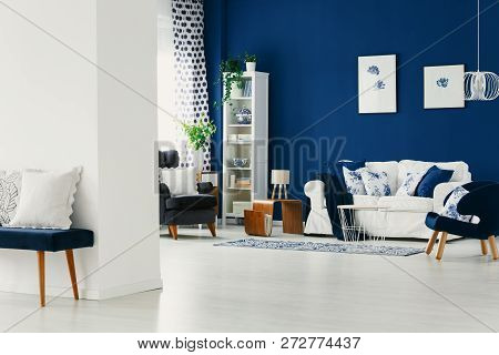 Classy Living Room With Dark Blue Wall, Comfortable Armchairs And White Sofa With Pillows, Real Phot