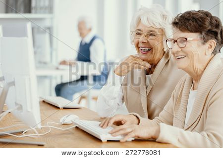 Two Smiling Senior Women With Glasses During Computer Classes For Elderly People