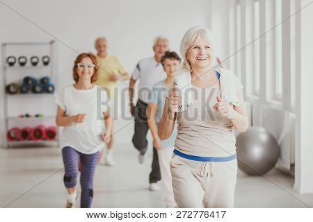 Happy Senior Woman With Towel Exercising During Fitness Classes For Elderly People