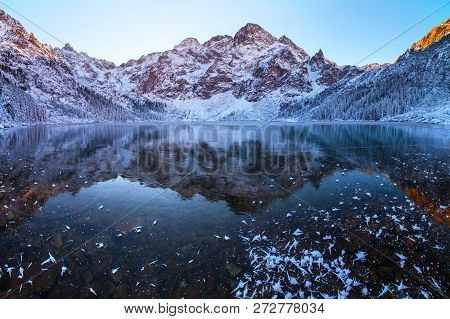 Winter Landscape. Mountains Reflected In Frozen Lake. Mountain Lake Covered With Clear Transparent I