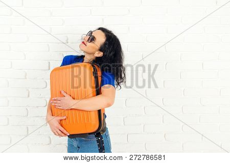 Happy Traveler Girl Hugging Her Orange Suitcase. Casual Girl Is Ready To Travel. Happy Woman In Drea