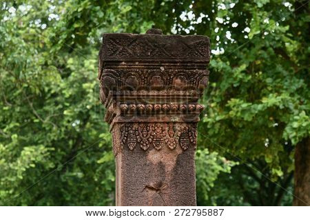 A Carved Sandstone Pillar In The Jungles Of Cambodia Surrounded By Large Trees
