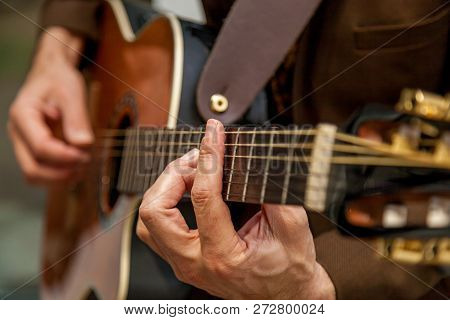Close-up Of The Hands Of A Musician Playing The Guitar. The Fingers Of The Musician Are Pressing The