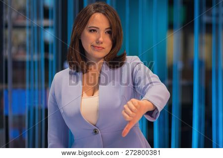Woman With Pessimistic Emotion In A Television Studio Shows A Gesture Of Fingers To The Bottom. Peop