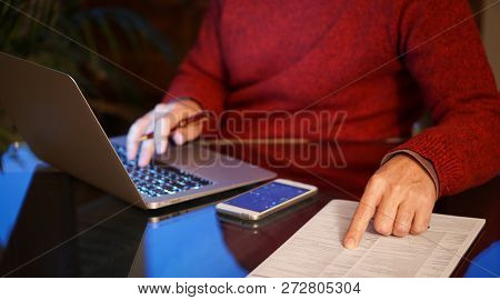 Man Using Laptop And Pointing To A Pressed Sheet