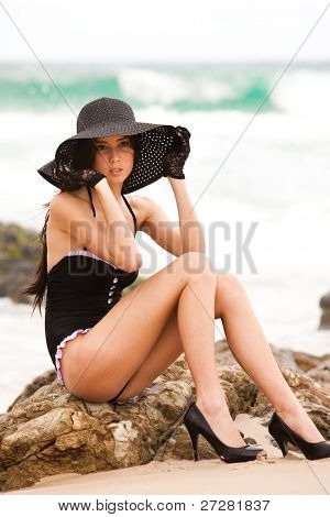 Portrait of an attractive young woman wearing a black one-piece swimsuit, hat, and lace gloves. She is sitting on rocks at the beach and staring off into the distance. Horizontal shot.