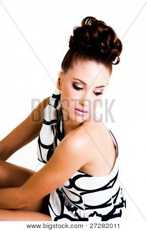 Portrait of a young woman. Her hair is styled in an updo and she is wearing a black and white dress, gloves and high heels. Vertical shot. Isolated on white.