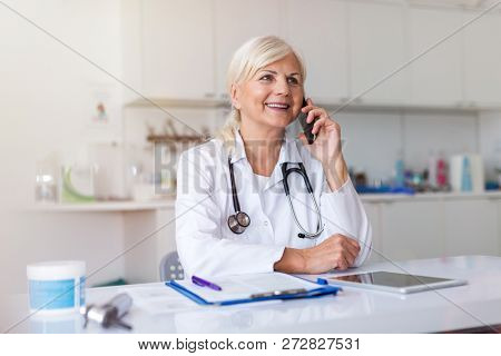 Female doctor using mobile phone in her office