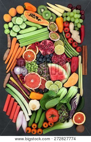 Health food choice for fitness with superfood of fresh fruit, vegetables, herbs and spice on slate background. Very high in antioxidants, anthocyanins, protein, vitamins and dietary fibre. Top view.