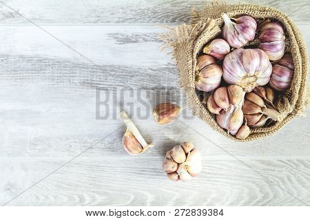 Garlic In A Sack Of Old Cloth. Fresh Garlic On A Light Gray Wooden Surface, Top View, Copy Space, Fr