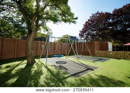 Modern Safe Playground With A Large Swing Rubber Mat And Astroturf In An Enclosed Yard On A Sunny Da