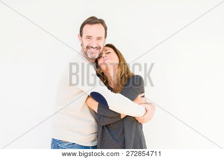 Beautiful middle age couple in love over isolated background Hugging oneself happy and positive, smiling confident. Self love and self care