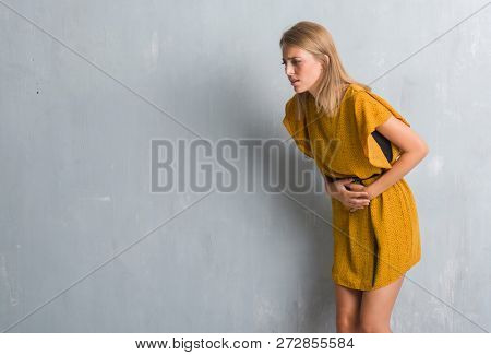 Beautiful young woman standing over grunge grey wall wearing a dress with hand on stomach because indigestion, painful illness feeling unwell. Ache concept.