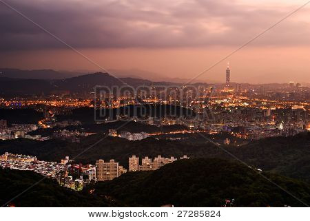 Taipei city night scene with illuminated buildings and famous skyscraper  under dramatic clouds in sky in Taiwan.