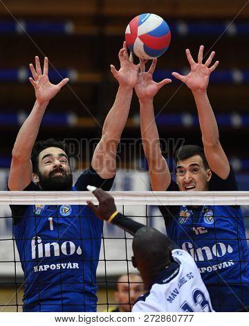 KAPOSVAR, HUNGARY – NOVEMBER 29, 2018: Jozsef Nagy (blue 1) blocked the ball at a Hungarian National Cup volleyball game between Kaposvar (blue) and MAV Elore (white) in Sportcsarnok Kaposvar.