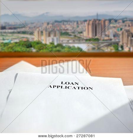 Loan application paper on desk near window and cityscape far away.