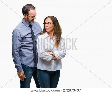 Middle age hispanic couple in love wearing glasses over isolated background with serious expression on face. Simple and natural looking at the camera.