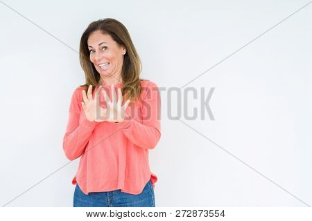 Beautiful middle age woman over isolated background disgusted expression, displeased and fearful doing disgust face because aversion reaction. With hands raised. Annoying concept.