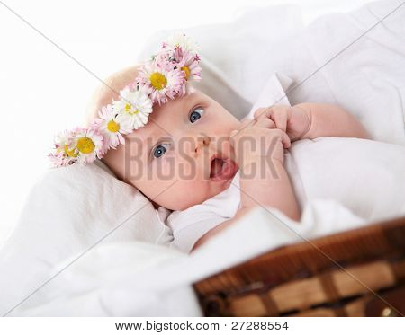 Portrait of a baby girl with a wreath of flowers on her head, in a brown basket