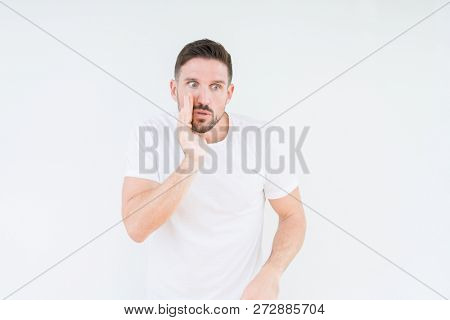 Young handsome man wearing casual white t-shirt over isolated background hand on mouth telling secret rumor, whispering malicious talk conversation