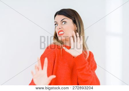 Young woman wearing casual red sweater over isolated background disgusted expression, displeased and fearful doing disgust face because aversion reaction. With hands raised. Annoying concept.