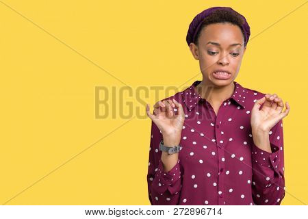 Beautiful young african american woman wearing head scarf over isolated background disgusted expression, displeased and fearful doing disgust face because aversion reaction. With hands raised