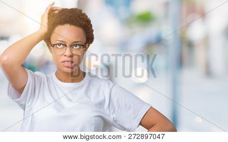 Beautiful young african american woman wearing glasses over isolated background confuse and wonder about question. Uncertain with doubt, thinking with hand on head. Pensive concept.