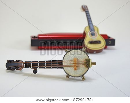 A Miniature Banjo And A Miniature Acoustic Guitar Propped Up On A Red 10-hole Diatonic Harmonica. In