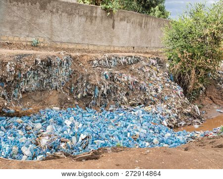 poster of A river in Ethiopia is clogged with empty plastic bottles, environmental disaster.