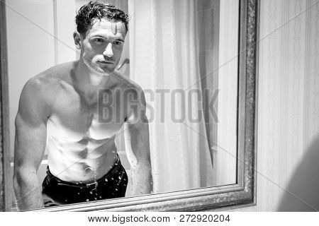 Handsome Shirtless Man With Muscular Body And Sixpack Abs Looking At His Reflection In Bathroom Mirr