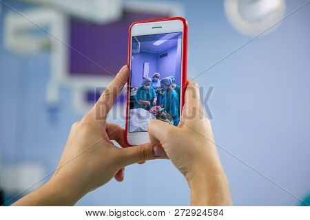 Assistant Shooting On The Smartphone From The Operating Room. Medical Team Performing Surgical Opera