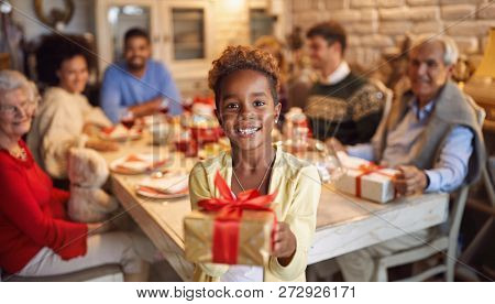 large happy family celebrate Christmas - Cute African girl giving x-mas present
